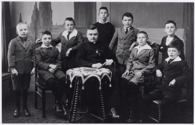 045511 - Kapelaan Bos met de misdienaars van de parochie St. Jans Onthoofding. Van links naar rechts ? Verbeek, Arnoud Appels (in 1947 overleden in Nederlands Oost-Indië), Kees Santegoets (werd slager in de Bergstraat), Janus van Croonenburg, bijgenaamd de lange Croon, Harrie van den Hout (werd beroepsofficier), Tiest van den Berg (werd pater), Chris Eijsermans (trad in bij de capucijnen en ontving daar de priesterwijding) en Antoon van Diem (later koster van de St.-Jan)