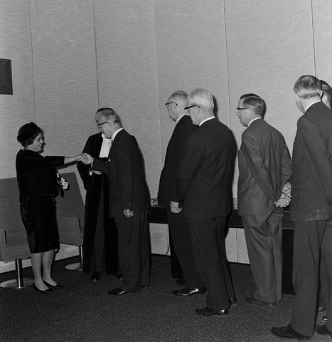 1237_004_001_008 - Hoger Onderwijs. Felicitaties. Professor Mr. Bronckhorst met zijn vrouw nadat hij een lezing heeft gehouden op de Katholieke Hogeschool in december 1964. De foto is genomen in het Jos Bedaux gebouw, het oudste gebouw van het huidige Tilburg University.