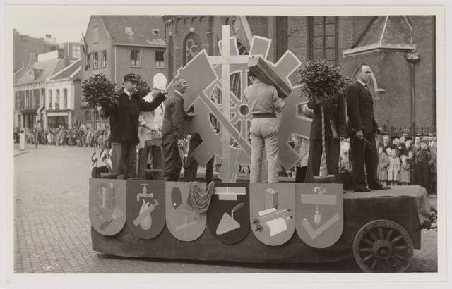 043137 - Wol- en bloemencorso b.g.v. het 10-jarig bevrijdingsfeest. Wagen voorstellend diverse ambachten door leden van de K.A.B.