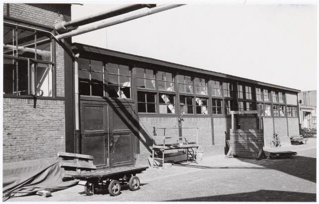 038649 - Volt.Zuid. Gebouwen. ±1950. Gebouw G uit 1928 met rechts het kantoor van het het productie-bureau, later Materials Management en midden de timmerwinkel. Het platte karretje op de voorgrond zag men in die tijd, met meerdere gekoppeld als een treintje, op en neer rijden naar de Piushaven. Daar werd plaatmateriaal geladen t.b.v. te maken transformatoren. Dit materiaal werd per schip aangevoerd.