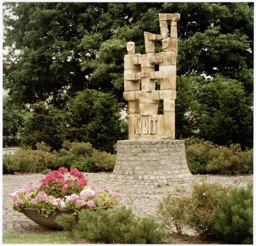 """039475 - Volt. Algemeen, Kunstwerken, Monument, Voltvonk. Ter vervanging van het relief in de zijgevel van het voormalige hoofdkantoor aan de Groenstraat, werd op het gazon tussen de hallen NA en ND op complex Noord op 27 maart 1980 een nieuw beeld onthuld. De benaming van het beeld was """"Voltvonk"""". Het is een ontwerp van de kunstenaar Paul Vincken verbonden aan het Keramisch Kollektief in Beersel ( Noord Limburg ). Het Keramisch Kollktief is een groep kunstenaars die verbonden zijn aan de Kleiwarenindustrie St. Joris aldaar. Het beeld is inmiddels geheel gerestaureerd en opnieuw opgebouwd op het Transvaalplein door de  Tilburgse kunstenaar Charles Vergouwen. De locatie ligt dicht bij de plek waar Volt in 1909 begonnen is. Op woensdag 30 oktober 2002 is de Voltvonk opnieuw onthuld door Burgemeester Stekelenburg en tegelijkertijd overgedragen aan de Gemeente Tilburg via een toespraak van de oud directeur van Volt, Ir. A. Hoevenaars."""