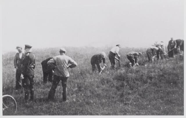 045585 - Goirlese werklozen aan het werk op de Regte Heide in het kader van de werkverschaffing. Links gemeenteveldwachter W. Jansen.