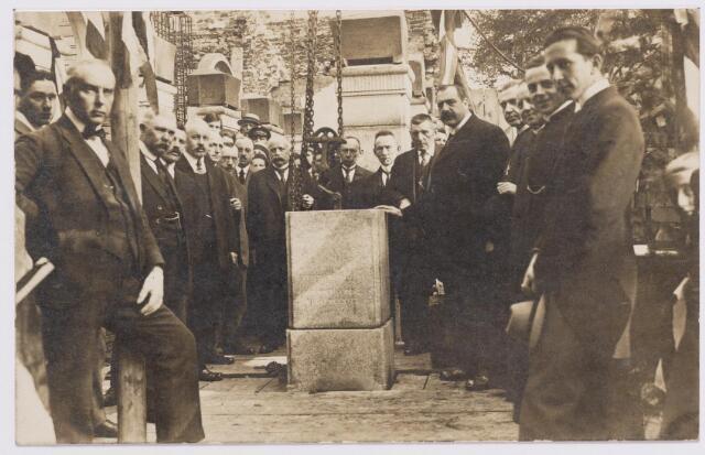 046630 - De eerste steenlegging van het gemeentehuis op de hoek Tilburgseweg-Kerkstraat. Het nieuwe raadhuis werd geopend op 20 augustus 1921. Het werd gebouwd onder architectuur van de Amsterdammer Th. Taen Err Toung, kleinzoon van de bekende architect dr. P.J.H. Cuypers. De aannemer was de Tilburgse firma W.F. Weijers. De bouwsom kwam op ruim 140.000 gulden. Nadat Taen in mei 1921 naar Nederlands Indië was vertrokken, werd zijn taak overgenomen door Eduard Cuypers. Op de foto rechts met een hand op de steen burgemeester J.B. Rens, links van hem wethouder A. de Brouwers. Links van de steen wethouder Vermeulen. Geheel rechts architect Th. Taen.