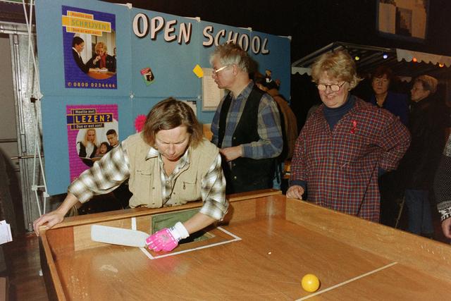 1237_001_037_007 - Een feestelijke bijeenkomst van Stichting Contour in Theater De Vorst (tegenwoordig theater de Nieuwe Vorst) in december 1997. Een soort tafelvoetbal op de informatiemarkt. Op de achtergrond informatie van de Open School over taalles.