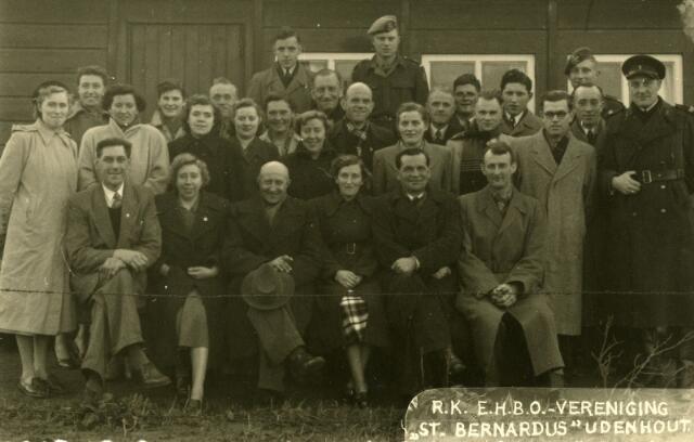 """071611 - R.K. E.H.B.O.-vereniging St. Bernardus te Udenhout. De foto is genomen bij het afscheid van Hanneske van Laarhoven (zittend derde van links) voor de barak, die stond op de """"kermiswaai"""", waar later de Eikelaar gebouwd is. Deze barak werd gebouwd door de Duitsers en deed dienst als gaarkeuken. In 1948 kocht de gemeente deze barak van het rijk en huisvestte er de EHBO en het Wit Gele Kruis. Hanneske van Laarhoven was kolenboer van beroep, maar emigreerde naar Australië, waar hij in 1977, 76 jaar oud, overleed.  Voraan rechts Kees Smits. De militair in het midden op de achterste rij is Wim Swaans, uiterst links met alpinopet Riet van Biljouw."""