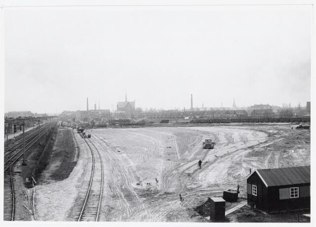 """036902 - Nederlandse Spoorwegen, NS, Belslijntje.: De aanleg van het """"Bels-lijntje"""" in 1958 ter hoogte van de Alleenhouderstraat. De foto is gemaakt vanaf de oprit Ringbaan-West richting station. Een gedeelte van de oversteek c.q. aansluiting """"Bels-Lijntje"""" is gereed. (zie ook 36900) Verder zien we het geegaliseerde spoorwegemplacement voor het nieuwe goederenstation. Voorheen was op een gedeelte rechts het oude NOAD voetbalveld."""