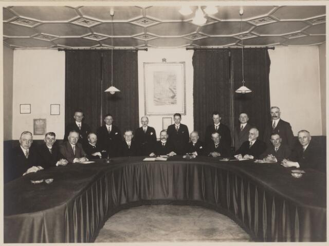 100378 - Gemeentepersoneel. Leden van de gemeenteraad in een buitengewone raadsvergadering bijeen ter gelegenheid van het afscheid van gemeentesecretaris C.P. Barel. Zittend v.l.n.r.Schumacher, H.T.A. de Kock, C. Martens, H. van Dijk, W.G. Oomen, burgemeester, secretaris C.P. Barel, C. Oomen, De Hoog, C.J.M. Rombouts en Jan Oomen (gemeentearchitect); staande v.l.n.r. C.A. Huybers, C.J. Zwaans, A.A. Abers, Roovers, P. Hijbrechts, J. Willems en C. A. Klaassen.