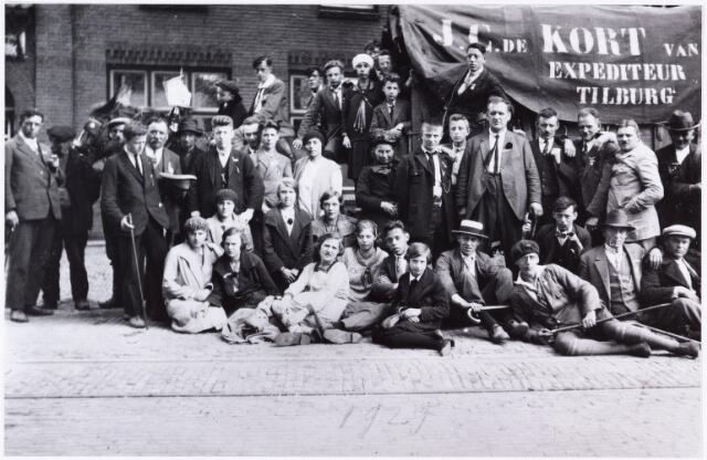 008825 - Bedevaartgangers van Tilburg naar Handel en Kevelaer. De vrachtwagen is van J.C. de Kort, expediteur Tilburg.  foto vlnr zittend: 2e C. Simons *1912, 5e M. Denissen *1914, 6e N. Vos *1914, 7e M. van Hest *1909, 8e L. van Rijswijk *1909, staand vlnr: J. Douwes, neven voerman L. van Rijswijk, achter C. Simons J. Douwes sr., G. Stalpers *1908, B. Donders, J. van Rijswijk * 1898, 5e van rechts A. Trimbach, daarboven een broer van pater Bleys, uiterst rechts J. de Kort leider van de processie.