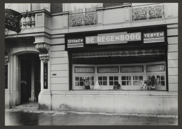 071887 - Een filiaal van stoomververij en chemische wasserij De Regenboog aan het Bezuidenhout 85 te Den Haag. De foto is afkomstig uit een album dat werd gemaakt en aangeboden naar aanleiding van het 40-jarig jubileum van textielfabriek De Regenboog van de firma Janssen en Bierens uit Tilburg op 2 december 1930.