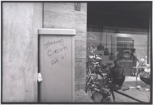 021940 - Graffiti op een meterkast bij de ingang van Vroom & Dreesmann in de Heuvelstraat