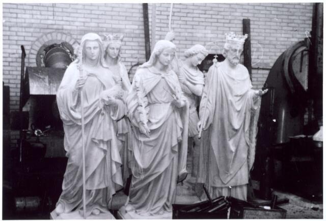 016053 - Beelden van het kerkhof aan de Bredaseweg staan in de werkplaats van smederij Vorselaars voor een grondige restauratie