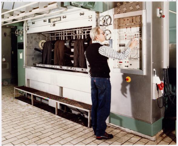 037966 - Textiel. Werknemer van wollenstoffenfabriek C. Mommers & Co. bezig met het instellen van een ultramoderne volkom