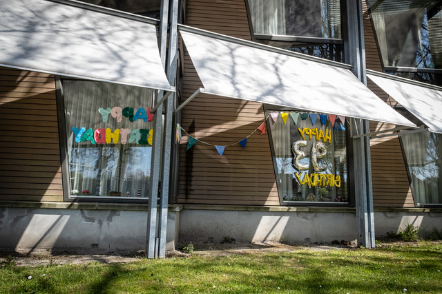 17280156 - Covid-19. Corona. Ziekten. Epidemieën. In zorgcentra en verzorgingshuizen mag geen bezoek meer worden ontvangen om zo het virus buiten de deur te houden. Om toch de 93ste verjaardag van een bewoner te vieren hebben familieleden verjaardagswensen op het raam geplakt. In spiegelbeeld, zodat het vanuit het zorgcentrum leesbaar is.