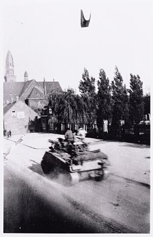 013270 - Tweede Wereldoorlog. Bevrijding. De eerste tank van de bevrijders rijdt de Laarstraat in. Rechts het kerkhof en op de achtergond de parochiekerk