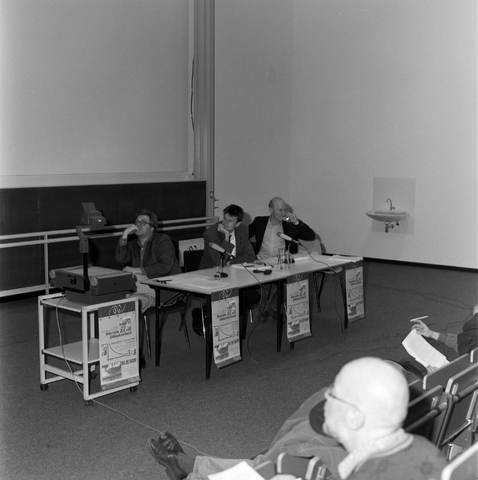 1237_001_006_004 - Hoger Onderwijs. De discussietafel in de collegezaal van de Katholieke Universiteit Brabant (tegenwoordig Tilburg University) tijdens een Studium Generale over sociale onzekerheid AOW.