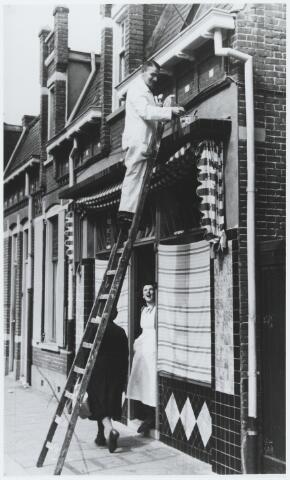 """056228 - Schilder Jos van Gorp werkzaam in de Molenstraat aan de textielwinkel """"Brewit"""" van de familie Brekelmans-Witters."""
