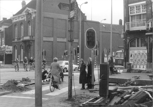 652474 - Straatbeelden van Tilburg. Wegwerkzaamheden aan de zuidkant van het Heuvelplein. Rechts een gesloten Hotel Riche met links er tegenover het pand van dr. Taminiau. Bij de stoplichten staat een mevrouw met een sjaal om haar hoofd - een mode item dat bij de meeste Nederlandse vrouwen buiten gebruik raakte sinds de jaren 70.