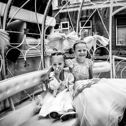 digi 1692_015 - Communiekantje met jonger meisje in een koetsje voor de communie. Feestelijke traditie in de wijk die in de volksmond bekend staat als de 'Vogeltjesbuurt'. De foto is onderdeel van een fotoserie van Anja van Eersel. Volksbuurt. Broekhoven. Groenewoud. Communiefeest