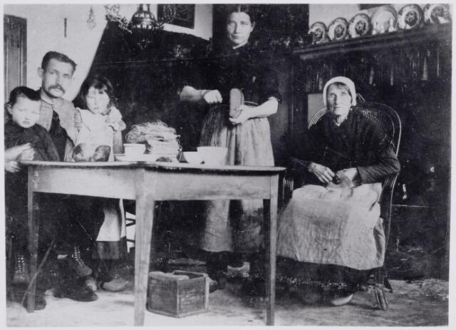 046043 - Interieur van het wevershuis van de familie Koolen in de Bergstraat. Links wever Johannes Franciscus (Frans) Koolen (1868-1936), die in 1890 trouwde met Maria van Osch, en zijn twee kinderen, Janus (1895-1921) en Jana (1892-1932). De laatste trouwde later met Jan van der Zande. In het midden zijn zuster Anna Catharina (Trien) Koolen (1860-1945), die ongehuwd bleef. Rechts hun moeder Johanna van Hees. Zij werd geboren te Goirle in 1828 en hertrouwde als weduwe van Jacobus Spaninks te Tilburg in 1856 met rietdekker Peter Koolen. Zij overleed in Goirle op 10 december 1902.