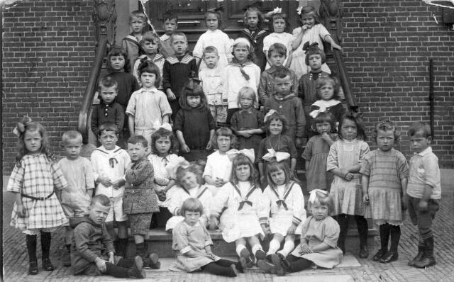 065805 - Onderwijs. Leerlingen van de bewaarschool  (later kleuterschool) van het r.k. kerkbestuur van de parochie Goirke op de trap naar de voordeur van de voormalige pastorie van deze parochie.