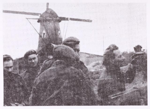 013224 - Tweede Wereldoorlog. Bevrijding. Militairen van de Prinses Irenebrigade te Hilvarenbeek staan op het punt Tilburg binnen te trekken. In de molen op de achtergrond bevond zich een Duitse uitkijkpost met mitrailleurs