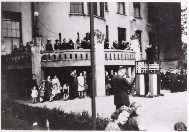 042726 - WOII; WO2; Het gemeentebestuur, met onder andere burgemeester Van de Mortel, op het balkon van het Paleis-Raadhuis tijdens de eerste Nationale Feestdag na de bevrijding.  Een dirigent geeft de toon aan.