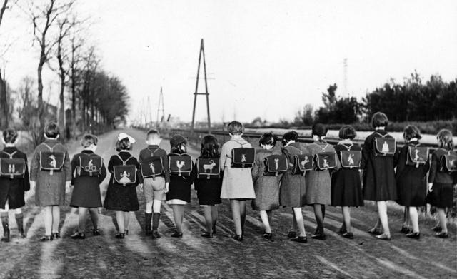 """1709_0007 - Schoolkinderen met rugzak op een rij vanaf de rug gezien. Kinderen van """"Bosvreugd"""", waar Marie-Louisa Franken-Enneking leidster was. Familie Franken-Donders."""