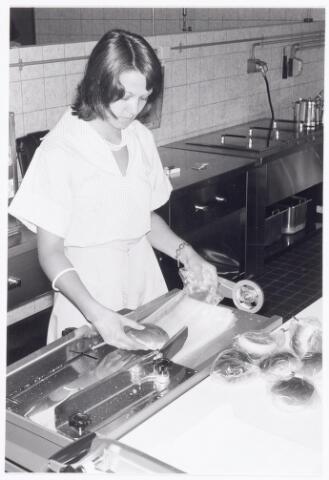 """038678 - Volt. Noord. Berijfsrestaurants. Vroeger kantine gebouw NL. Voorverpakken van broodjes met de """"blaaszakmachine"""" in mei 1976."""
