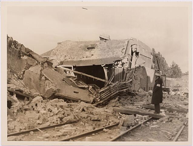 013164 - Tweede Wereldoorlog. Vernieling werkplaats NS. Een brandwachter van de Luchtbeschermingsdienst waakt bij de ruïne van de in puin geschoten NS-werkplaats om plundering te voorkomen. Vooral de kolenvoorraad op het terrein was onder de bevolking gewild