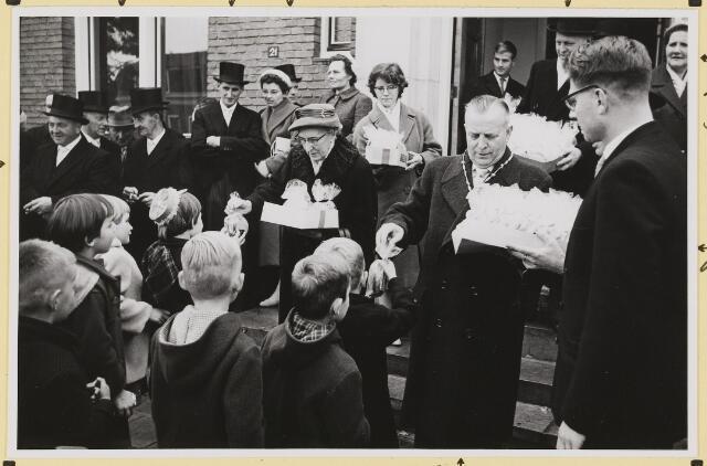 072869 - Afscheid burgemeester J.H. Bardoel.  Uitdelen van traktaties aan de schoolkinderen. In het midden de heer en mevrouw Bardoel. Links: A. Rijnen (Met sigaar), J. v. Laarhoven, echtpaar Wolfs-Op 't Hoog, Rechts: G. Klomberg, mevr. Rijnen- Kastelijns, Th. v. Delft.