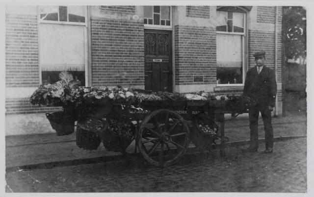 """040316 - Antonius A. Van Rijswijk met zijn groetekar voor zijn woonhuis in de Elzenstraat (nu Prunusstraat. Hij had een handel in zaad, groente en fruit aan de Elzenstraat nr. 90. De foto moet genomen zijn voor zijn huwelijk in 1931. Op de foto vent hij groente voor zijn moeder de wed. P van Rijswijk, """"hovenier"""""""
