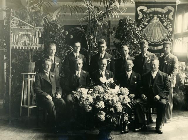 656357 - Kerkelijk erkende fietsbedevaart Tilburg-Kevelaer. Groepsfoto van het bestuur ter herinnering aan het 25-jarige kerkelijk goedkeuren op 24 juni 1934. Bestuur: voorzitter J. van Ham, secretaris J. de Jong, penningmeester J. Verhoeven, comm. J. Adams en P. Jongen. Feestcommissie, L. van Langerijt, Jo Vugts, F. Wellens, V. Dona, G. Foucier, A. Bomenberg.