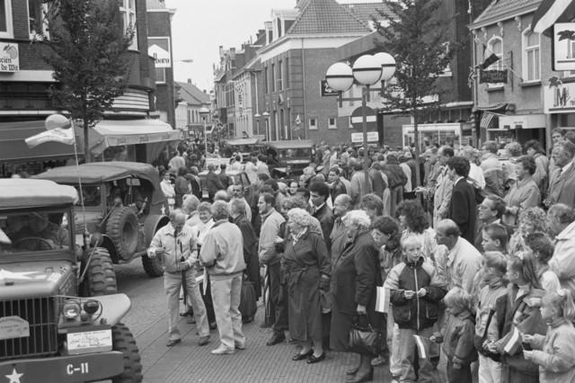 """TLB023000119_003 - Toeschouwers en militaire voertuigen uit de 2e Wereldoorlog tijdens een parade ter gelegenheid van de Bevrijdingsfeesten in 1989. Opname gemaakt op het, in de volksmond genoemde, """"Radiopleintje"""""""