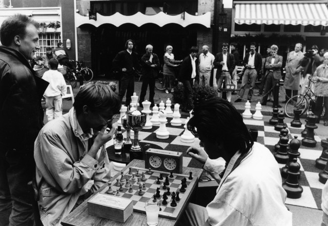 1238_F0096 - Schaaktoernooi in de stad. Op de voorgrond twee geconcentreerde spelers. Op de achtergrond geïnteresseerd publiek..