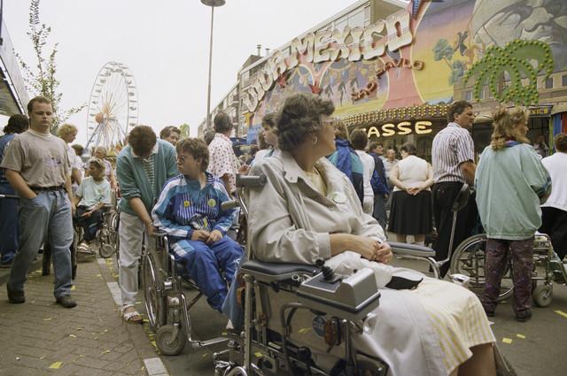 TLB023000074_003 - Bezoekers in rolstoel voor kermisattractie tijdens gehandicaptenmiddag.  De Tilburgse Kermis is de grootste kermis in de Benelux. Er staan jaarlijks tussen de 230 en 240 attracties uit binnen- en buitenland, in een 4,5 kilometer lang lint door het centrum van de stad. De kermis trekt jaarlijks meer dan een miljoen bezoekers en is daarmee een van de best bezochte evenementen van Nederland.