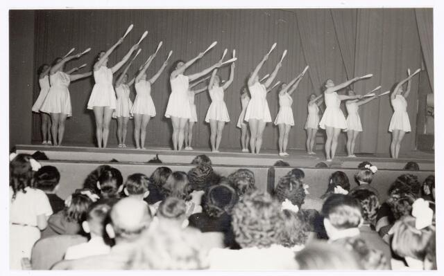 038818 - Volt. Sport en ontspanning. Jaarlijkse uitvoering van gymnastiekver. Volt in de bovenzaal van de Metropole Schouwburg. Later werd deze traditie voortgezet in de nieuwe schouwburg aan de Schouwburgring. Hier een knotsoefening. tijdvak 1951 of 1952.