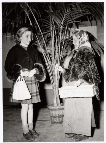 """039350 - Volt. Zuid. Hulp-Afdelingen, Sociale Zaken, Zorg. Ontspanning. Vertelmiddag van Mw. Pim Siegers op 24 februari 1951. Hier wordt een sketch gedaan door Jopie Bierhof als """"Appelvrouwtje"""", en Suzanne van Elten als """"klein Mevrouwtje""""."""