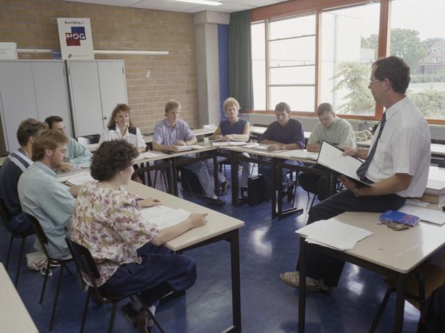 TLB023000100_002 - Leerlingen met leraar in klaslokaal. Foto ter promotie van opleidingen in Tilburg en t.b.v. Onderwijsexpositie
