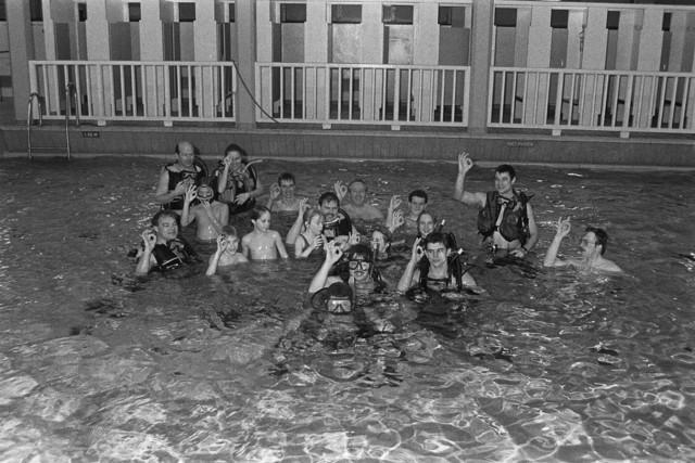 TLB023002475_003 - Duikers en een groepje zwemmers samen in het zwembad aan de ringbaan oost te Tilburg