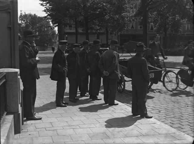 652130-bew - Straatbeeld. mannen met hoeden en petten staan voor de pastorie. een handkar en enkele fietsers passeren op straat.