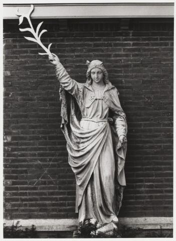 067902 - Stenen gevelbeeld van de HEILIGE URSULA, aangebracht in de zijgevel van de kapel van het voormalige Ursulinenklooster in de Elzenstraat, afgebroken in 1981. De H. Ursula, maagd en martelares, was een (Engelse?) koningsdochter uit de 4e eeuw. De palmtak is het algemene attribuut van de martelaren van de kerk. Het specifieke attribuut van de H. Ursula is niet meer aanwezig: de pijl waarmee zij werd vermoord is uit haar rechterhand verdwenen. Maker en atelier: onbekend.   Trefwoorden: Kerkelijke kunst, openbare ruimte.