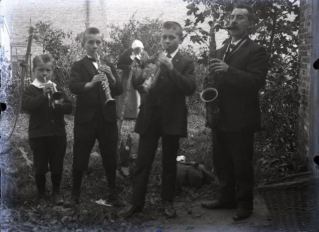 651572 - Man en kinderen met instrumenten. Trompet, saxofoon en klarinet. De Bont. 1914-1945.