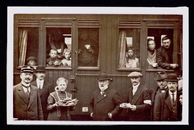 1696095 - Het Nederlandse Rode Kruis. Eerste Wereldoorlog. WOI. In 1914 kwamen in Tilburg 13.000 Belgische vluchtelingen aan. Zij werden opgevangen door vrijwilligers van het Belgische vluchtelingen comité en door leden van het Rode Kruis. Vluchtelingen in een trein worden verwelkomd met boterhammen.