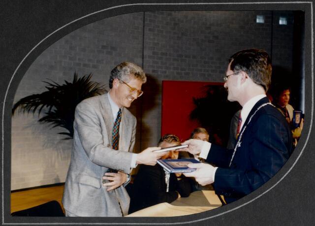 """91284 - Made en Drimmelen. De burgemeester van Made de heer J. Elzinga (1990-1997) deelt het boek """"Zo'n echte Ark van Noë"""" uit tijdens de opening Sociaal Cultureel Centrum """"De Mayboom"""" in Made."""