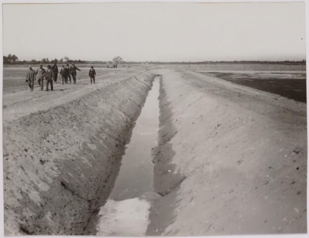 040837 - Werkverschaffing voor werklozen. Bezoek van minister van Binnenlandse Zaken en Landbouw mr. J.B. Kan (1873-1947). Een afvoersloot, waarin de drainagebuizen het gereinigde fabriekswater naar lager gelegen gemeenten afvoert. Rechts een veld met vuilwater bevloeid.