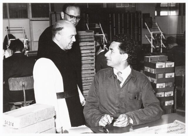 038661 - Volt. Zuid. Bezoek Paters Trappisten aan Volt op 23 juni 1958. Op de foto Pater Christianus in gesprek met medewerker  v. Puijenbroek van de fabricage- of productie-afdeling Spoelen. Achteraan Pater van den Broek (Avé Maria), bedrijfsaalmoezenier.