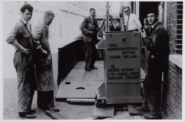041738 - Elisabethziekenhuis. Gezondheidszorg. Ziekenhuizen. Een container cobalt-60 wordt met de lier op een laadbak geplaatst. De zending was bestemd voor het zogenaamde Witte Huis, een radiotherapeurische instituut van het St. Elisabethziekenhuis, gelegen op de hoek van de Prof. Dondersstraat en de Jan van Beverwijckstraat. Dit huis was eens het woonhuis van burgemeester Van Voorst tot Voorst en tegenwoordig de bestuurszetel van de stichting Het R.K. Gasthuis. Ten tijde van deze foto was in het Witte Huis het RTIT, Radio Therapeutisch Instituut Tilburg, gevestigd (1953-1981). De man in het witte overhemd is Jan Boïnk, tweede van links Kees van Besoijen magazijn-chef van Boïnk-Meijer, uiterst rechts Frans van de Sande. Links vooraan Jan van Ras, monteur bij Boink Meijer.