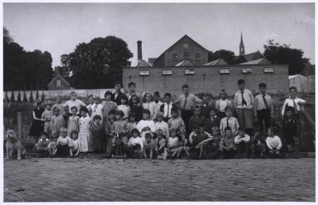 022899 - Buurtkinderenaan de achterzijde van de fabriek van Janssens van Buren, aan de Jan Heijnsstraat, omstreeks 1932. Op de achtergrond de paterskerk aan de Gasthuisstraat.
