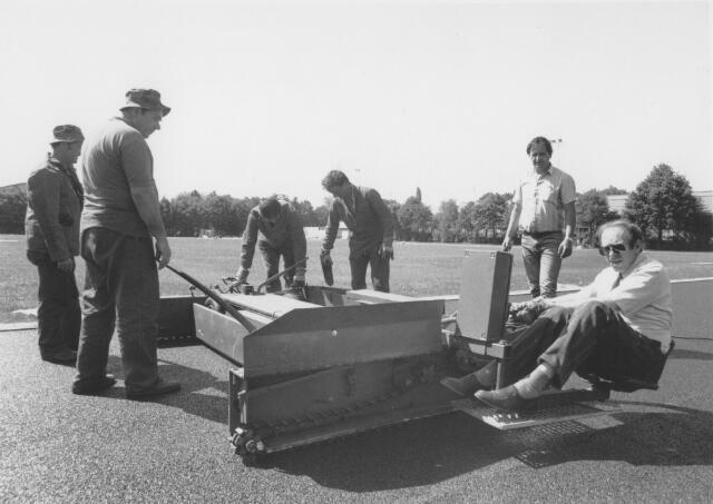 065707 - Het aanbrengen van een nieuwe toplaag op de atletiekbaan. Rechts op de voorgrond wethouder Timmermans.