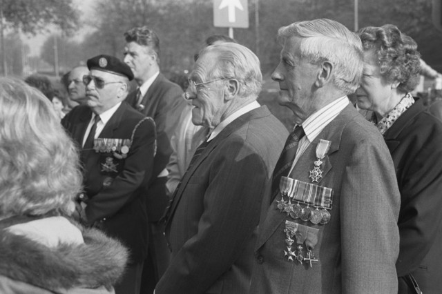 TLB023000111_001 - Gedecoreerde veteranen tijdens de Bevrijdingsfeesten 1989 bij het Verzetsmonument & Kapel Onze Lieve Vrouw van Altijddurende Bijstand, ter herdenking van de gevallenen tijdens hevige gevechten op 26 en 27 oktober 1944 in de wijk Broekhoven.